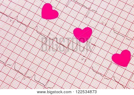 Hearts of paper lying on electrocardiogram graph, ecg heart rhythm, medicine and healthcare concept