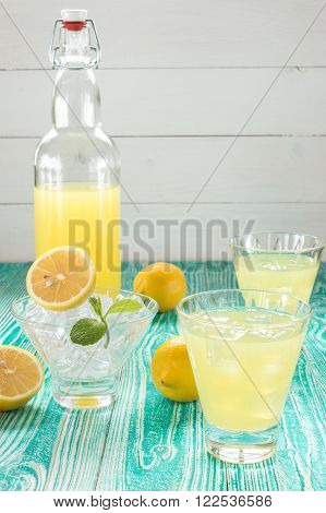 lemonade or limoncello in glasses with ice cubes sherbet glass with ice cubes decorated by mint leaf lemon fruits on turquoise colored wooden table