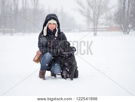The portrait of a girl with black dog on the snowfield