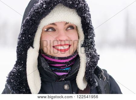 Closeup portrait of young happy woman in the earflaps and hood