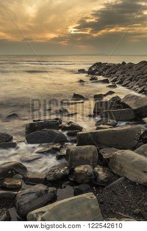 Beautiful Sunset Landscape Image Of Rocky Coastline In Kimmeridge Dorset England