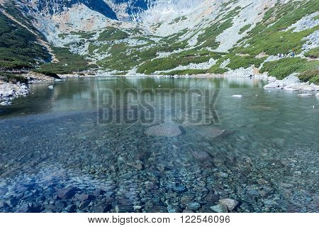 Fall colors reflected in a lagoon in the High Tatras Mountains