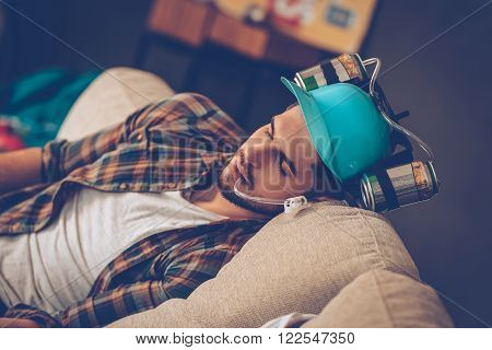 Sleeping beauty. Close-up of young handsome man in beer hat napping on sofa in messy room after party