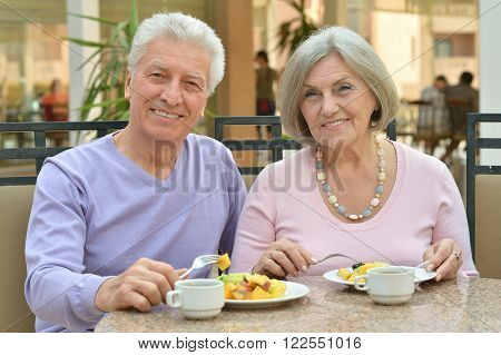 Happy mature couple eating dinner at restaurant