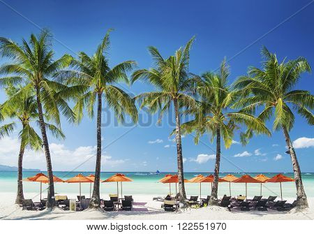 white beach lounge bar chairs and umbrellas on boracay tropical exotic island in philippines