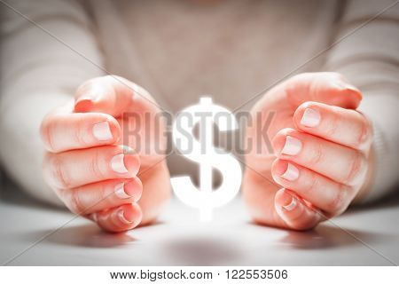 Dollar sign between woman's hands in gesture of protection. Concept of currency rate stability, finance.