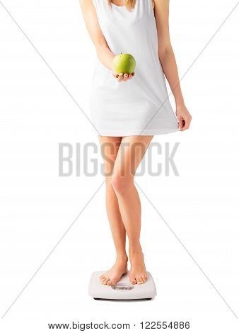 Woman standing on weight scale with apple in her hand