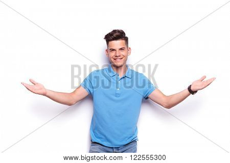 close up portrait of handsome young man in jeans and blue polo shirt welcoming with open arms while looking at the camera in white isolated studio background