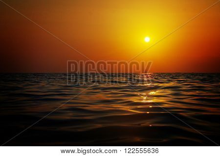 Sunset reflecting on the southern Italy sea, a stretch of land with a lighthouse is visible low on the horizon.