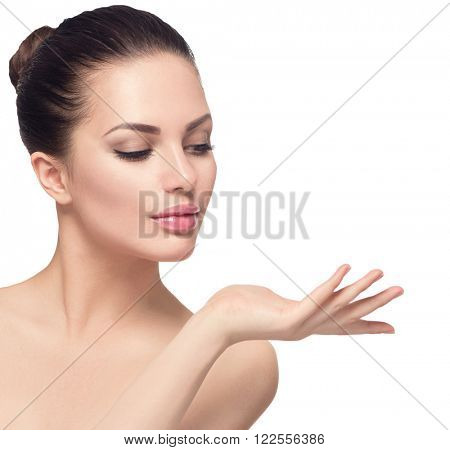 Beauty Spa Woman with perfect face skin Portrait. Beautiful Brunette Spa Girl showing empty copy space on the open hand palm for text. Proposing a product. Gesture for advertisement. Isolated on white