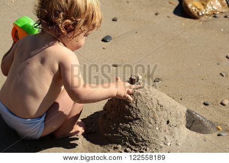 Little curious smart blonde baby boy sitting on sea coast outdoor playing with wet beach sand building tower on natural sunny background, horizontal picture