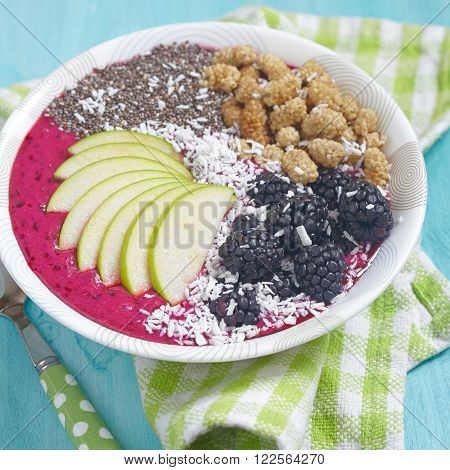 Acai bowl smoothie topped with apples, berries, coconut and chia seeds