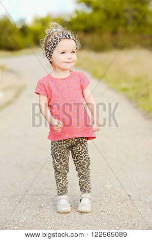 Smiling baby girl 2-3 year old wearing stylish leopard print pants and trendy top outdoors. Walking in park.
