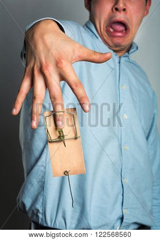Businessman's hand in the mousetrap