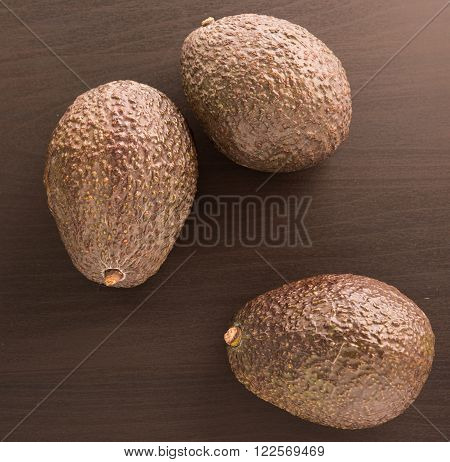three fresh Avocados on a black background