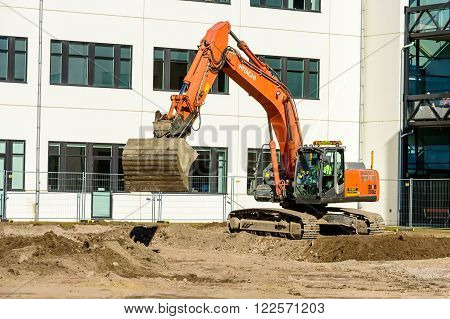 Kalmar Sweden - March 17 2016: An orange Hitachi Zaxis 350LC excavator digging outside the university building. Scoop in the air just above the ground. The university is growing.