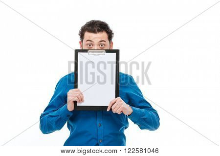 Young man pepping from blank clipboard isolated on a white background