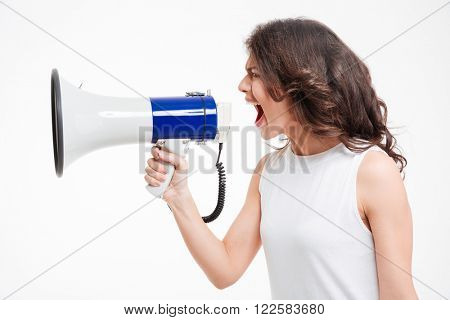 Side view portrait of a young woman screaming into megaphone isolated on a white background