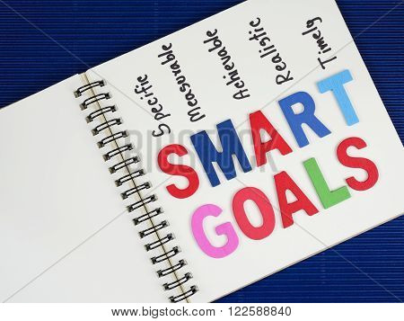 SMART Goals on blank notebook with blue corrugate paper background (Business Concept)