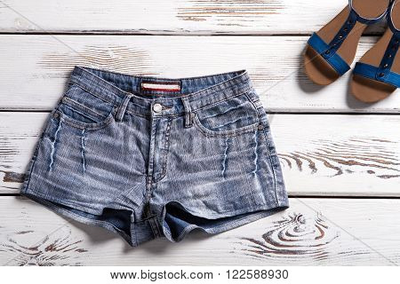 Woman's denim shorts and sandals. Shorts and footwear on shelf. Simple shorts and summer footwear. Summer clothes from new catalog.
