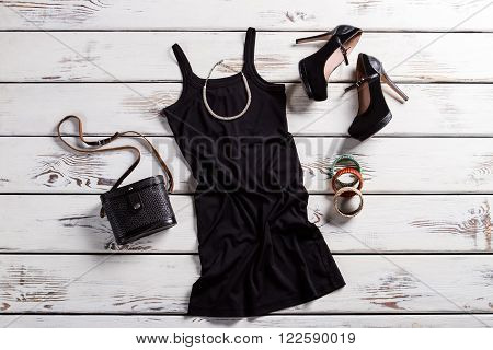 Black dress, shoes and jewelry. Black female outfit on table. Glamorous dark clothes with purse. Retro purse and modern clothing.