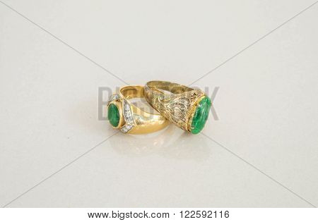 Closeup old green jade rings on blurred marble stone floor texture background