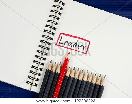 Red pencil standout from black pencil and handwriting word Leader on wood background, leadership business concept poster