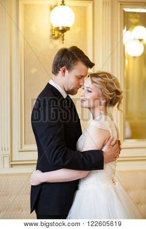 Hugging wedding couple in a bright room