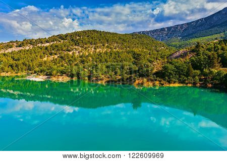 Mountain canyon Verdon in the French Alps. Smooth emerald green water of Lake Sainte-Croix-du-Verdon reflects the sky and wooded shore