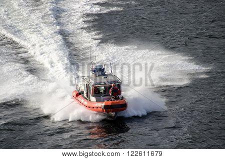 Ketchikan Alaska USA - June 13 2013: US Coast Guard 25-foot Defender-Class boat escorts a cruise ship out of Ketchikan