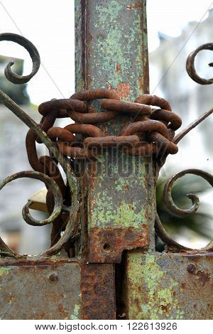 A closeup of a rusty chain wrapped around a rusty gate