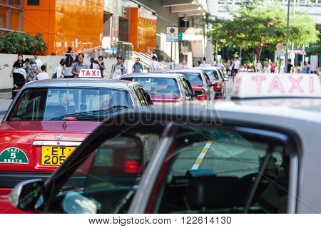 HONG KONG - JULY 28: A fleet of Hong Kong taxis waiting outside the Tseung Kwan O MTR in New Territories July 28, 2015. Hong Kong taxis are easily recognizable by their red and white colors.