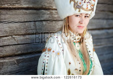 Portrait of a young woman in traditional dress of the peoples of South Siberia, against the wall of timber.