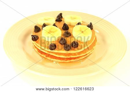 Breakfast from Pancakes garnished with slices banana chocolate chips with added Maple Syrup served porcelain dish over white