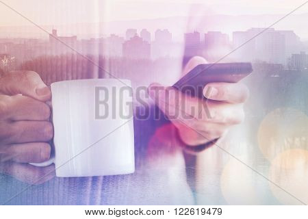 Casual man reading SMS text messages on his smartphone and drinking coffee in the morning multilayered double exposure image with bokeh light and selective focus.