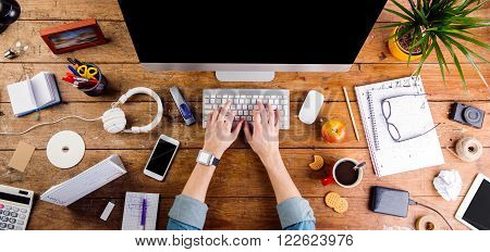 Business person working at office desk. Smart watch on hand and smart phone on the table. Coffee cup, notepad and glasses and various office supplies around the workplace. Flat lay.