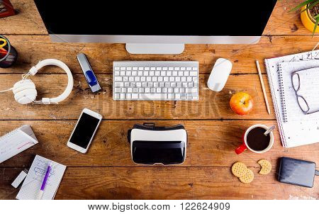 Desk with various gadgets and office supplies. Computer, smart phone, virtual reality goggles and stationery around the workplace. Flat lay.