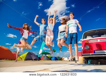 Group of teenage boys and girls at summer music festival jumping by vintage red campervan poster