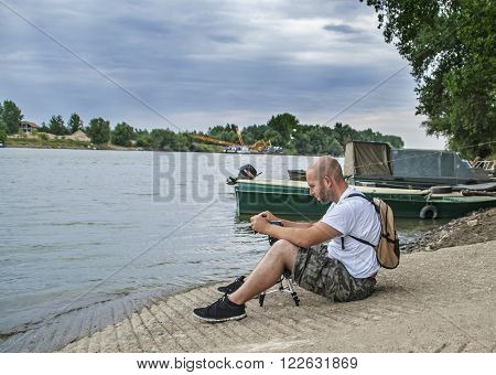 Photographer sitting on the shore and photograph the river that flows quietly.