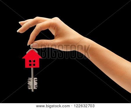 Woman's hand holding house key with keychain in the form of home isolated on black background