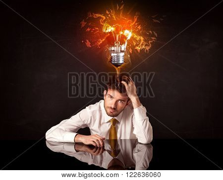 Depressed businessman sitting under a blowing idea bulb