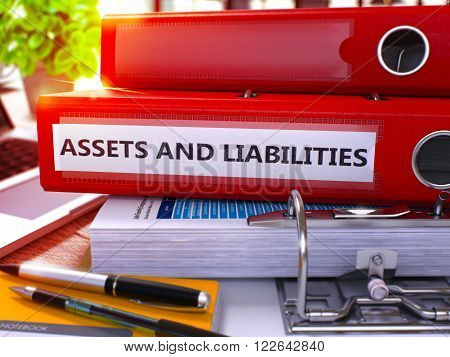Red Office Folder with Inscription Assets and Liabilities on Office Desktop with Office Supplies and Modern Laptop. Assets and Liabilities Business Concept on Blurred Background. 3D Render.