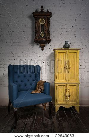 Still life of vintage blue armchair yellow cupboard pendulum clock and orange ornate scarf in studio