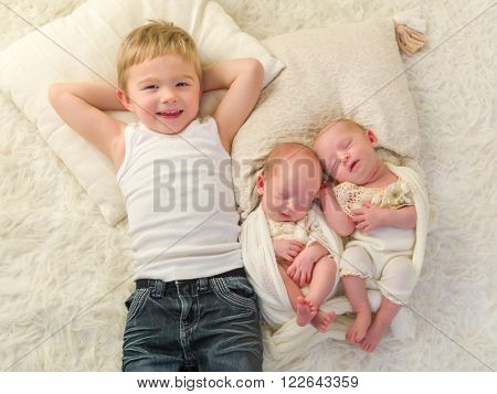 Proud little toddler boy posing with his newborn identical twin sisters