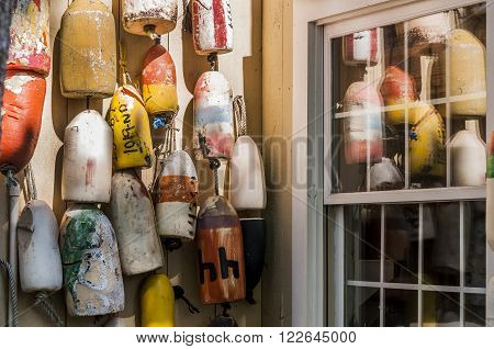Old colorful lobster buoys against a weathered cedar shake wall.