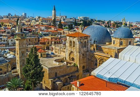 The grey domes and bell tower of the Church of the Holy Sepulchre and the slender minaret of the Mosque of Omar seen from the bell tower of the Lutheran Kirche of the Redeemer Israel.