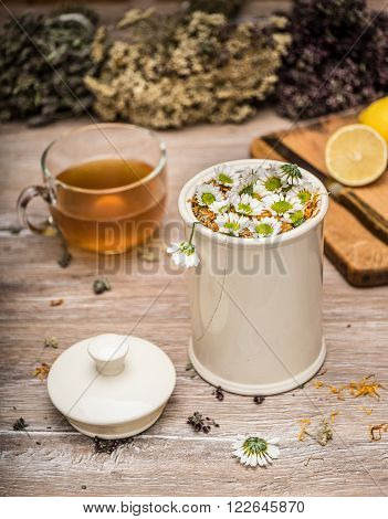 Medicative herbs in a ceramic can and in bunches tea in a glass cup a lemon and a knife on a chopping board.