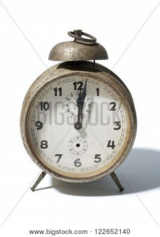 Old rusty antique alarm clock close up isolated on white background.