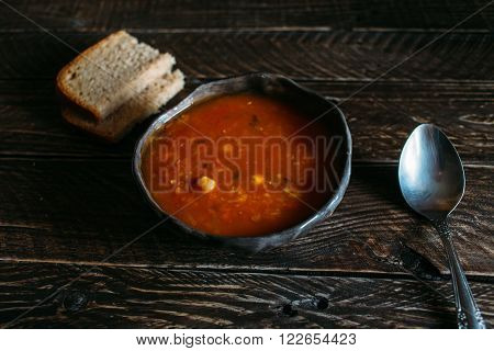 Tomato soup with chickpeas and lentils lentil soup in an earthenware pot** Note: Visible grain at 100%, best at smaller sizes
