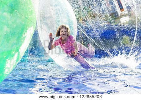 Young girl playing inside a floating water walking ball.